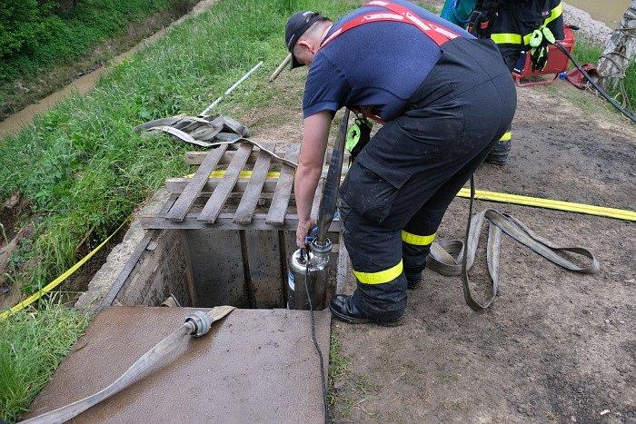 Hasiči čerpali vodu z přehrady na Opavsku a čistili odtok v narušené hrázi, květen 2021.