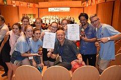 Členové novojičínského pěveckého sboru Ondrášek s diplomy, které získali v soutěži v Tokiu. Uprostřed je sbormistr a umělecký vedoucí Josef Zajíček.