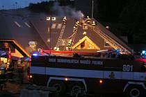 Hasiči likvidují požár střechy rozestavěného hotelu.