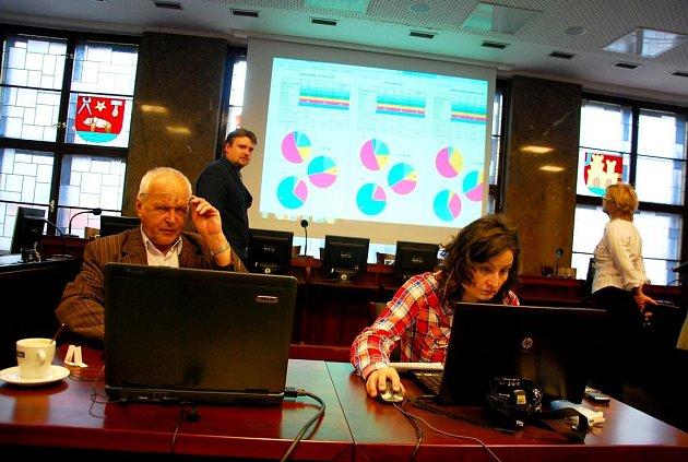 Starosta Jaroslav Dvořák (stojící vlevo) sleduje vývoj elektronické aukce.