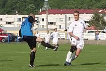 Brankář Fulneku Pospěch odkopává míč před dotírajícím útočníkem Slovácka Chmelíčkem.