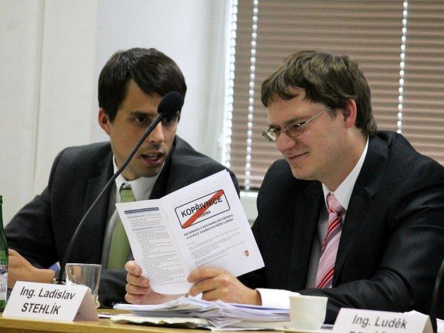 Zastupitel Ladislav Stehlík nahlíží do materiálu, který má obyvatelům ubiny objasnit některá fakta. Diskutuje s ním kolega Tomáš Hof.