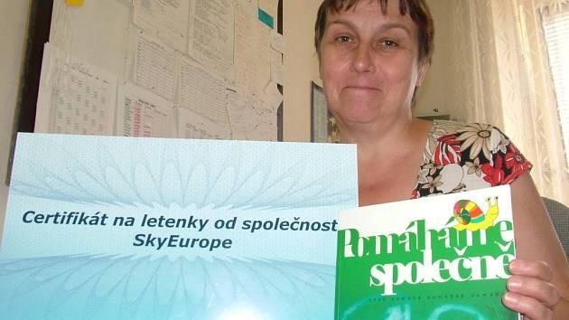 Naďa Kadrnožková ukazuje certifikát na letenky pro děti z zylových domů, které se díky němu podívají do zahrničí.