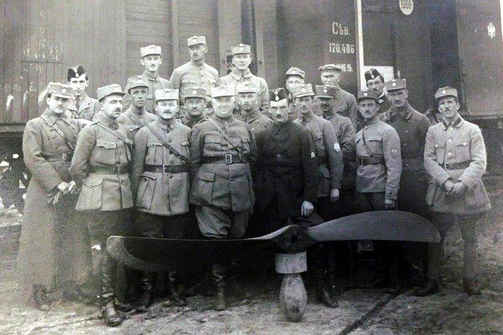 Kapitán Melč mezi československými legionáři - oblečen v důstojnický frenč, na levém rukávu má hodnostní označení, na hlavě ruskou pilotní lodičku pro důstojníky vzor 1914, s bílo-červenou stužkou a sdruženým znakem čs. odboje, rok 1919.