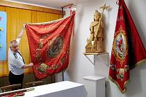 Starosta hasičů Štramberku Pavel Kalíšek ukazuje starý prapor s vyobrazeným svatým Floriánem. Vpopředí čeká na posvěcení jeho replika.