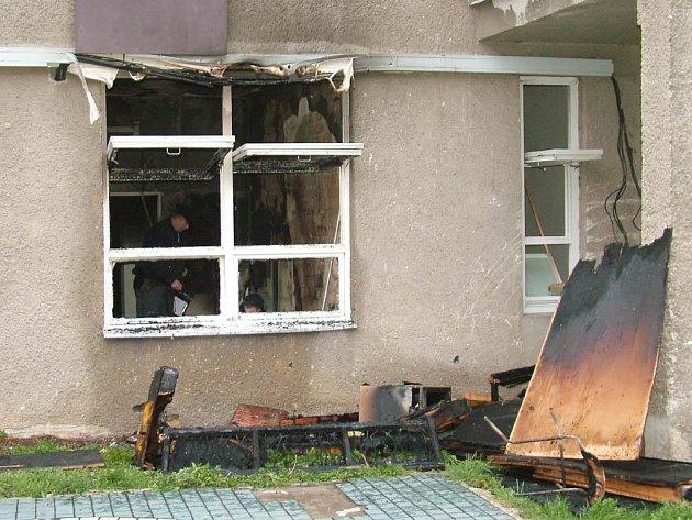 Policista s technikem hasičů prozkoumávají vyhořelý byt na Dvořákově ulici v Novém Jičíně.