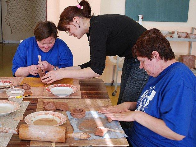 Terapeutka Tereza Müllerová pomáhá Ivaně Maroňové v modelování keramiky. Vpravo další z klientek terapeutických dílen Jitka Pospíšilová.