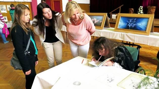 Návštěvníci suchdolského kulturního domu sledují Johanku Pascale při kreslení ústy.
