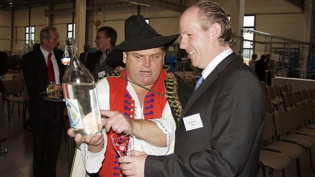 Majitel podniku Rieger Automotive International Veit Schuler při otevření závodu dostal darem slivovici od Valašského vojvody Olina Kutáče.