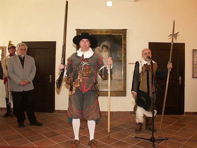 Člen skupiny historického šermu Les Enfants Perdus jako mušketýr předvádí na vernisáži nabíjení muškety za přítomnosti autora výstavy Jiřího Juroka (vlevo) a vedoucího skupiny Jana Langera.