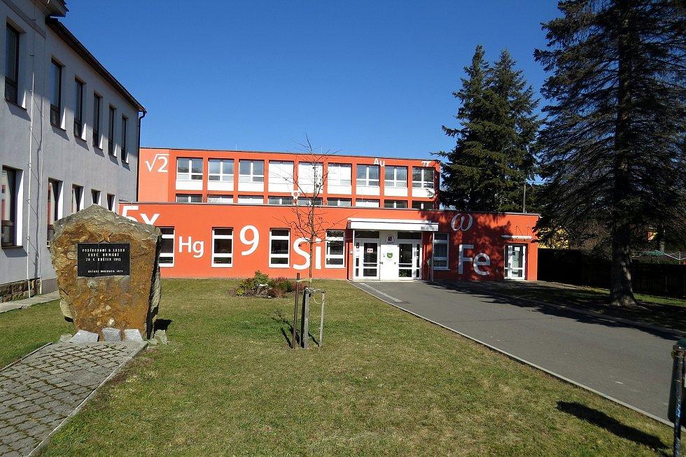 Fasádu základní školy v Mořkově zdobí také chemické a matematické značky.