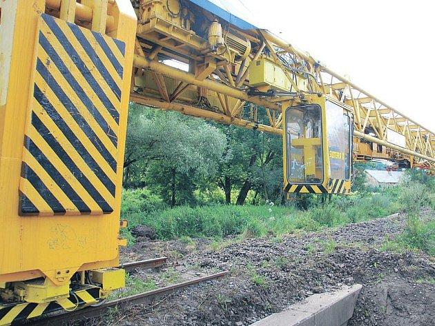 Pracovní stroje na poničené železnici.