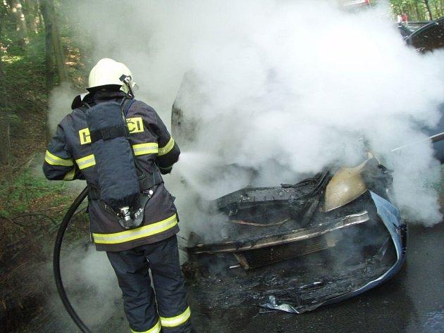 Hasiči při hašení požáru automobilu.