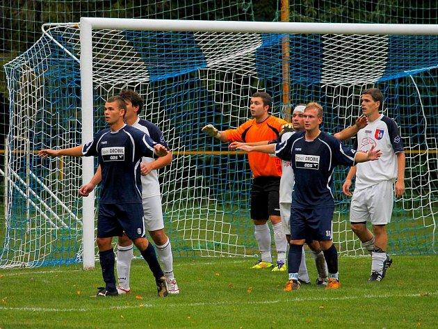 Fotbalisté Petřvaldu (světlé dresy) se v domácím utkání neprosadili. Na snímku se snaží obrana domácích, v čele s brankářem Kotrbou, zabránit jedné z útočných akcí Raškovických.