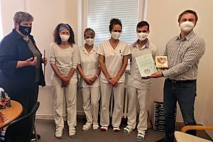 Bílovečtí zdravotníci s krajkovými srdíčky. Vlevo stojí zástupkyně krajkářek Světlana Marková.