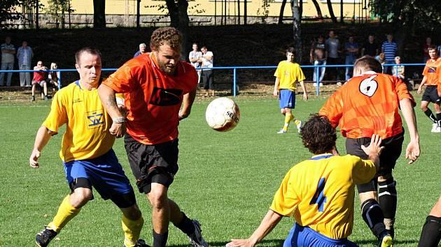 Záložník Žarošic Lukáš Přikryl (v oranžovém) se snaží přejít přes dvojici bránících hráčů Veselí. Celek z Kyjovska doma vstřelil šest branek a vyhrál 6:2.