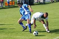 Kapitán Baníku Dubňany Milan Dohnálek (v bílém) bojuje o míč s vlkošským obráncem Valentou.