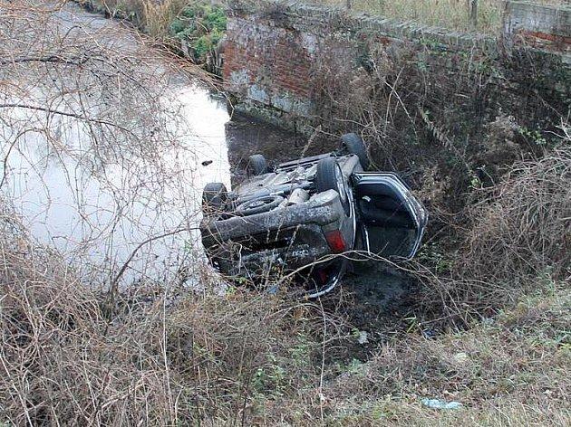 Řidič po smyku spadl do vody.