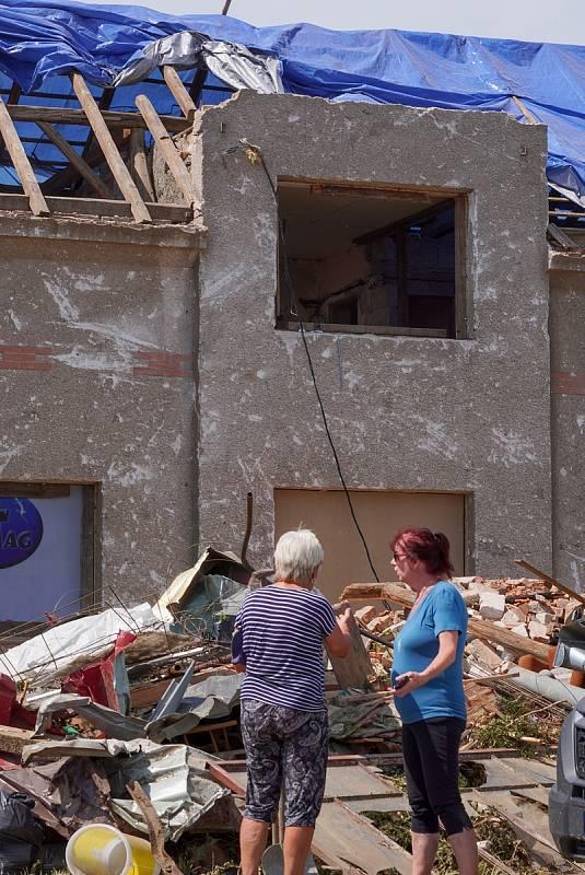V Mikulčicích na Hodonínsku je poškozeno asi 300 domů. Provizorně opravené střechy zmodraly díky plachtám, u kulturního domu je i trikolóra a nechybí česká vlajka. O víkendu dorazily do tornádem poničené vesnice stovky dobrovolníků, pomáhají s likvidací n