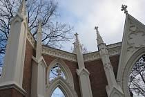 JAKO PŘED STO LETY. Na bráně vyniká štít s rosetovým motivem nad lomeným obloukem vchodu. Ze stran ji lemují pilíře s fiálami.