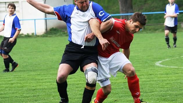 Stoper Žarošic Zbyněk Poláček (vlevo) se přetahuje o míč s útočníkem Mikulčic Štefanem Šimkem.