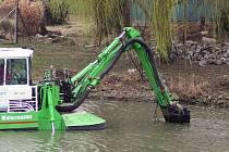 Speciální sací bagr čistí rybník v Mikulčicích. Kalnou vodu vypouští do vytvořené laguny.