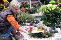 Lidé uklízeli kolem hrobů na hřbitovech a zdobili je věnci a svíčkami.