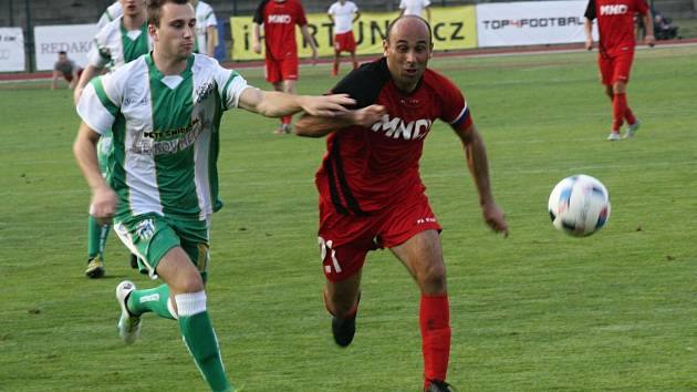 Hodonínští fotbalisté (v červených dresech) ve vloženém 15. kole divize D porazili Bzenec 2:0 a osamostatnili se v čele tabulky. Derby na stadionu U Červených domků sledovalo 520 diváků.