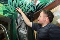 Malíř Petr Přikryl maluje v pavilonu ptáků v hodonínské zoo.