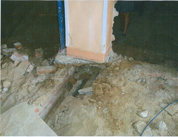 Snímek ukazuje nosný sloup, který drží jen minimální vrstva betonu nad kanalizací.