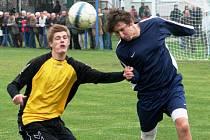 Stoper Hroznové Lhoty Petr Laga (v modrém) odvrací hlavou míč před dotírajícím útočníkem Kněždubu Davidem Grabcem.