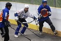 Útočník Rigumu Hodonín Michal Tóth (v bílém) bojuje za brankou soupeře proti přesile, vpravo je hokejista SHK Matěj Charvát.