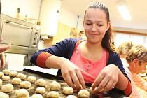 Příprava na tradiční hody v Kněždubu. Členové chasy spolu s místními ženami pečou hodové koláčky.