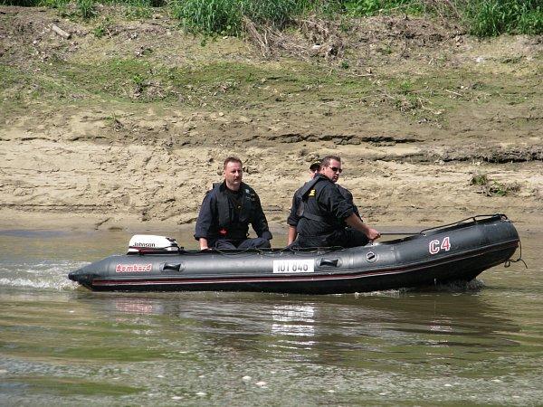 Pátrání hasičů a policistů uOsypaných břehů, místa, kde se předpokládá, že se trojice hledaných dostala do vody.
