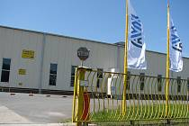 Areál ještě zdobí staré cedule po MWG. U brány už ale vlají vlajky nového majitele AVX.