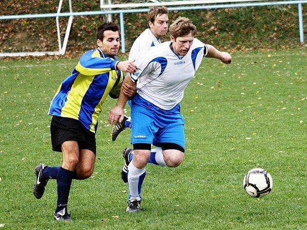Kapitán Sobůlek Michal KOnečný (v bílém) se snaží zastavit útočníka Vlkoše Gabriela Davida. Domácí tým vyhrál ve 14. kole okresního přeboru 3:0.