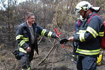 Hasiči se nyní pohybují po spáleništi se speciální pěnou na zádech.