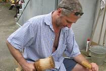 Řezbář z Lipova Lubomír Sedlář na dvorku rodného domu vyřezával v létě 2010 část dřeveného kříže umístěného později v Žarošicích na Silničné.