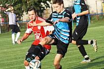 Útočník Blatnice Patrik Janík (v červeném) bojuje o míč s kyjovským stoperem Martinem Riedlem.