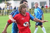 Fotbalista Ratíškovic Tomáš Voříšek (v červeném) v zápase s Mutěnicemi.