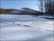 Ostrov uprostřed řeky skrývá led a sníh.