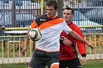 Kyjovský záložník Zdeněk Bartoň (v bílém) si kryje míč před dotírajícím ratíškovickým obráncem Petrem Kordulou. Baník doma v derby prohrál 0:2.