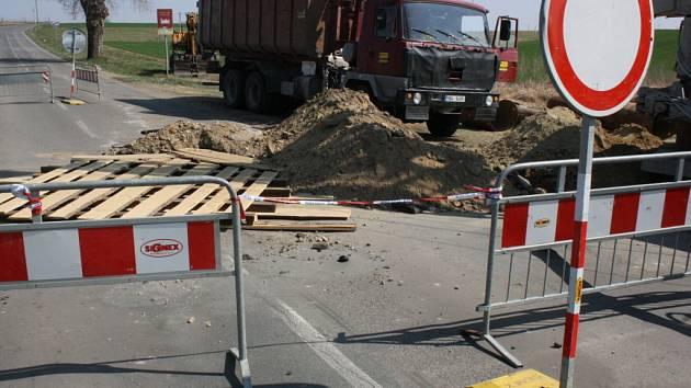 Kolem propadlé silnice v Šardicích projíždějí auta.