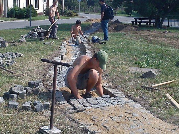 Čejkovičtí mladíci dláždí chodník parku, který sami postaví.