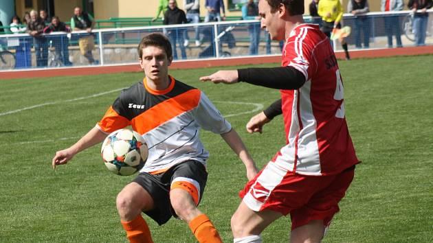 Záložník Kyjova Martin Riedl (v bílém dresu) se snaží zastavit hráče Dražovic. Nedělní utkání 16. kola 1. A třídy skupiny B skončilo remízou 2:2.