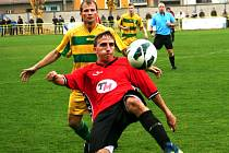 Ratíškovický záložník Lukáš Koplík (v červeném) se snaží odehrát míč před dotírajícím středopolařem Mutěnic Zdeňkem Štěpanovským.