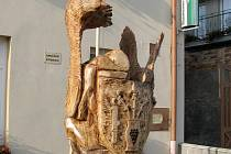 Od sjezdu rodáků zdobí Nenkovice dřevěná socha, na které se dravci snaží odnést obecní znak.