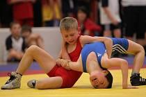 Mladý hodonínský zápasník Alexandr Lucký (v červeném dresu) v jednom ze soubojů přehodil pomocí točené záruče svého soupeře do nebezpečné lopatkové pozice.