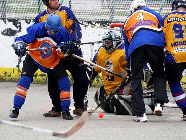 Útočník TJ Gladiators Hodonín Jiří Hynšt (uprostřed) se snaží prosadit ve skrumáži před brankářem Vlků Milanem Fialou.