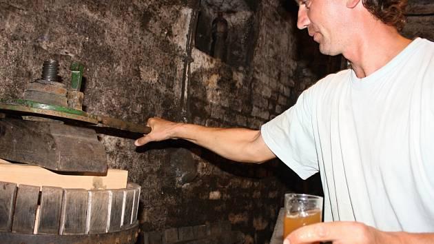 Milan Ingr presuje bílé hrozny na lisu ze třicátých let dvacátého století. Připravuje tak burčák pro kamarády a přátele, kteří k němu přijedou příští víkend.